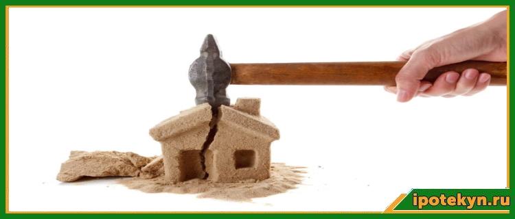 удар молотком по песчаному домику